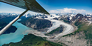 """Seen from the air, Riggs Glacier drains into the fjord of Muir Inlet in the East Arm of Glacier Bay National Park, in Alaska, USA. Flightseeing from Skagway or Haines is a spectacular way to see Glacier Bay. We were bedazzled by Mountain Flying Service's 1.3-hour West Arm tour from Skagway. Glacier Bay is honored by UNESCO as part of a huge Biosphere Reserve and World Heritage site shared between Canada and the United States. In 1750-80, Glacier Bay was totally covered by ice, which has since radically melted away. In 1794, Captain George Vancover found Icy Strait on the Gulf of Alaska choked with ice, and all but a 3-mile indentation of Glacier Bay was filled by a huge tongue of the Grand Pacific Glacier, 4000 feet deep and 20 miles wide. By 1879, naturalist John Muir reported that the ice had retreated 48 miles up the bay. In 1890, """"Glacier Bay"""" was named by Captain Beardslee of the U.S. Navy. Over the last 200 years, melting glaciers have exposed 65 miles of ocean. As of 2019, glaciers cover only 27% of the Park area. Since the mid 1900s, Alaska has warmed 3 degrees Fahrenheit and its winters have warmed nearly 6 degrees. Human-caused climate change induced by emissions of greenhouse gases continues to accelerate warming at an unprecedented rate. Climate change is having disproportionate effects in the Arctic, which is heating up twice as fast as the rest of Earth. This image was stitched from multiple overlapping photos."""