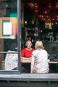 Women chat in the window of a bar in Hoxton, Shoreditch<br /> Shoreditch, an area that was dominated by light industry is now home to cafes and fashionable restaurants and cafes