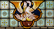 Stained glass window Bedingfield church, Suffolk, England, UK c 1878, detail of pelican feeding its young with its own blood, prob Heaton, Butler and Bayne