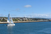 A Private Yacht Sails Through the Entrance Channel in Newport Beach with Corona del Mar in the Background
