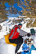 Backcountry skier in a kitchen shelter, Inyo National Forest, Sierra Nevada Mountains, California
