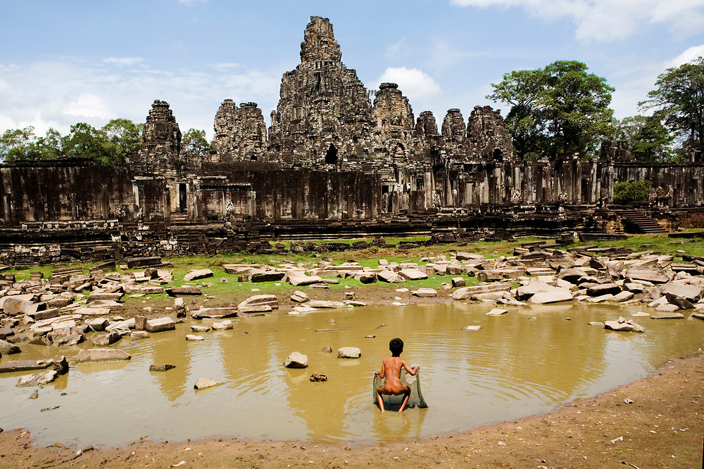 Angkor Thom: a skinny little boy fishing in the rubble-filled city moat using a torn fish net; Bayon temple face towers beyond.
