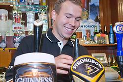Young Polish barman pulling a pint of beer at Polish Social Club,