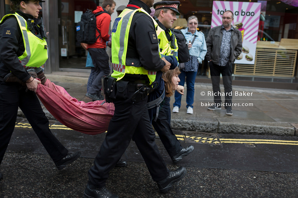 An environmental protester is arrested under Section 14 of the Public Order Act after chaining themselves together and glueing body parts to the road in Fleet Street on the 11th and final day of protests, road-blockages and arrests across London by the climate change campaign Extinction Rebellion, on 25th April 2019, in London, England.