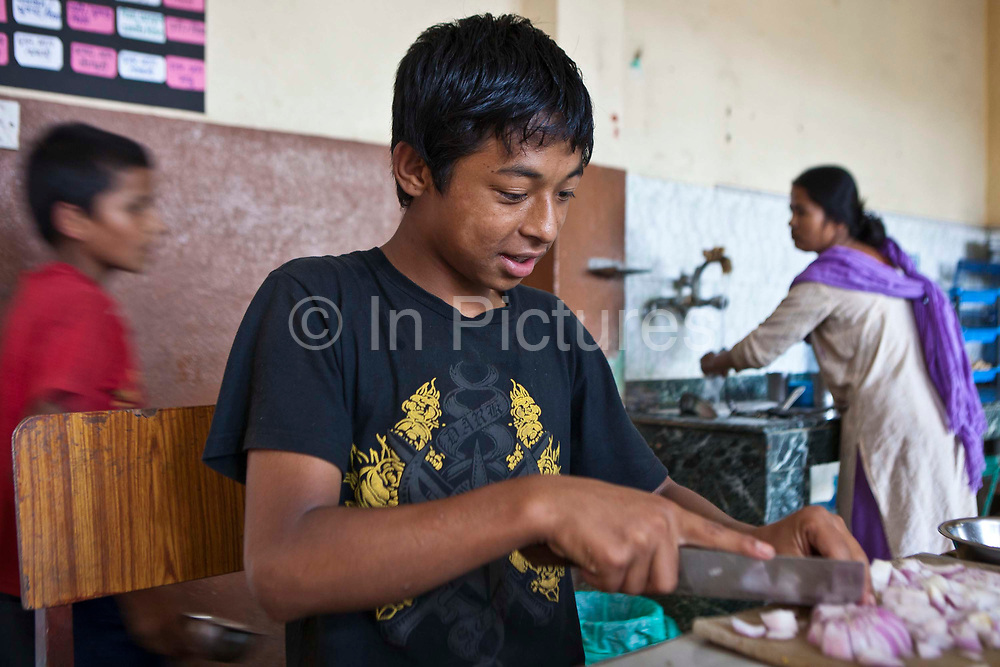 A young Nepalese boy chops an onion while helping out in the kitchen at Voice of Children rehabilitation center in Kathmandu, Nepal.  The not-for-profit organisation supports street children and those who are at risk of sexual abuse through educational and vocational training opportunities, health services and psychosocial counseling.