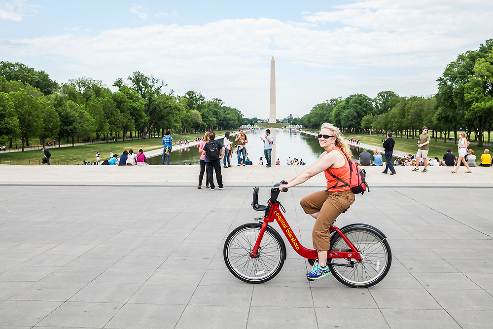 A happy woman riding a bike share bike on the National Mall in Washington D.C., USA. The Washington Monument in the background.