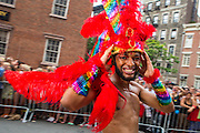 A marcher wearing a brightly colored feathered headdress marches down Christopher Street.