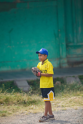 Central America, Nicaragua, Granada.  Young boy waiting to catch ball during baseball game.