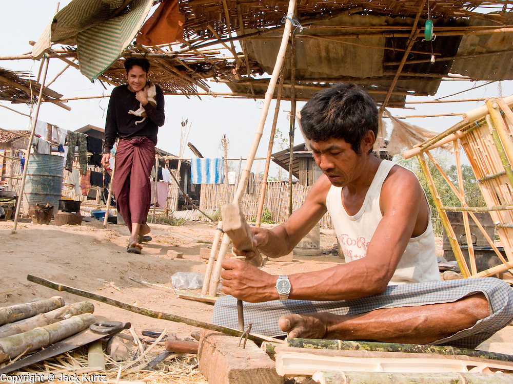26 FEBRUARY 2008 -- MYAWADDY, MYANMAR: A man makes bamboo furniture for sale in the market in Myawaddy, Myanmar. Myawaddy, a town of about 65,000, is just across the Moei River from Mae Sot, Thailand and is one of Myanmar's leading land ports for goods going to and coming from Thailand. Most of the businesses in the town are geared towards trade, both legal and illegal, with Thailand. Human rights activists from Myanmar maintain that the Burmese government controls the drug smuggling trade between the two countries and that most illegal drugs made in Myanmar are shipped into Thailand from Myawaddy.   Photo by Jack Kurtz