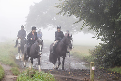 Licensed to London News Pictures. 09/10/2021. London, UK. Horse riders enjoy the dense fog on Wimbledon Common south-west London this morning as the Met Office issue yellow weather warnings for fog patches in London and the South East, leading to difficult driving conditions and disruption to travel. Photo credit: Alex Lentati/LNP