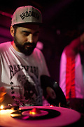 Male Brazilian DJ selector playing vinyl records in a club with low lighting. Digital Dubs dub reggae dancehall soundsystem at Leviano Bar, Lapa, Rio de Janeiro, Brazil