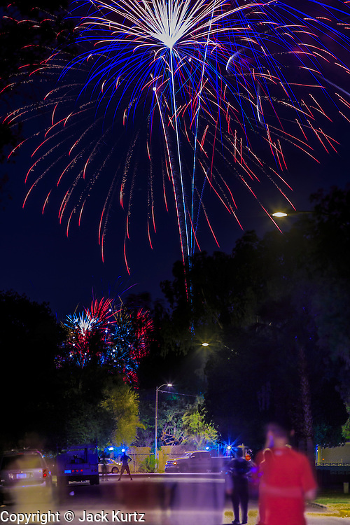 04 JULY 2012 - PHOENIX, AZ:   People stand in the middle of a residential street in central Phoenix and watch the 4th of July fireworks show at the nearby Phoenix Country Club, a private development in the center of the city. July 4 marked the 236 birthday of the United States.  PHOTO BY JACK KURTZ
