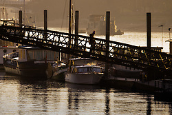 London, February 24th 2016. A woman crosses onto the Chelsea houseboat moorings as the sun rises on a chilly but clear London morning. ///FOR LICENCING CONTACT: paul@pauldaveycreative.co.uk TEL:+44 (0) 7966 016 296 or +44 (0) 20 8969 6875. ©2015 Paul R Davey. All rights reserved.