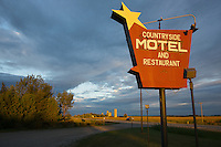 Motel sign in rural countryside near Strathroy, Ontario Canada with early morning light and a dramatic sky.