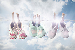 Pair of baby shoes hanging on clothes line, Bavaria, Germany
