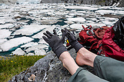 Gloves on toes at ice-filled Crucible Lake in Mount Aspiring National Park, Southern Alps, Otago region, South Island of New Zealand. Beginning in the Siberia Valley, the Crucible Lake Track departs from the Gillespie Pass Circuit about an hour above the Siberia Hut. UNESCO lists Mount Aspiring as part of Wahipounamu - South West New Zealand World Heritage Area.