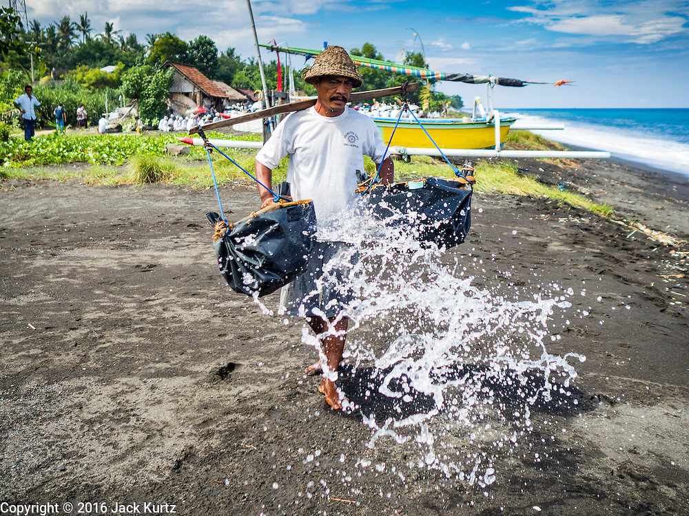 20 JULY 2016  - KUSAMBA, BALI, INDONESIA: A man sprinkles sea water in his salt making area on the beach in Kusamba. Salt makers in Kusamba, on the Bali coast, make salt by sprinkling sea water on a bed of sand and scraping up the salt when the water evaporates. It's a very slow, labor intensive way of making salt.       PHOTO BY JACK KURTZ