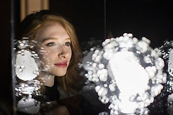 © London News Pictures. 03/02/2017. Tamsin Huggins 22 poses with Zika virus glass sculpture. Luke Jerram's Glass Microbiology exhibition on display at At-Bristol. The exhibition showcases eight jewel-like sculptures, showing accurate representations of deadly viruses and microbiology. Photo credit: Brad Wakefield/LNP
