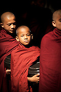Young monks queue for their only meal of the day at the Maha Gandaryon Monastery, near Mandaly, Myanmar