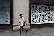 A shopper walks past a window display that features numbers - part of a design theme called State of the Arts, at the Selfridges department store on Oxford Street, on 4th March 2019, in London England. Darren Almonds piece 'Chance Encounter 004', consists of a grid formed from rectangular panels, featuring fragmented numbers that appear to scroll across the surface. <br /> State of the Arts is a gallery of works by nine crtically-acclaimed artists in Selfridges windows to celebrate the power of public art. Each of the artists are involved in creating a site-specific artwork at one of the new Elizabeth line stations as part of the Crossrail Art Programme.