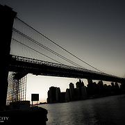 Shadowy view of the Brooklyn Bridge and the Manhattan skyline as the sun goes down.