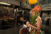 A woman waearing a hat decorated with fresh carrots takes a break to order a hot dog from a street vendor on 5th Avenue.