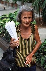 Woman working on Havana street selling paper cones of roasted peanuts,