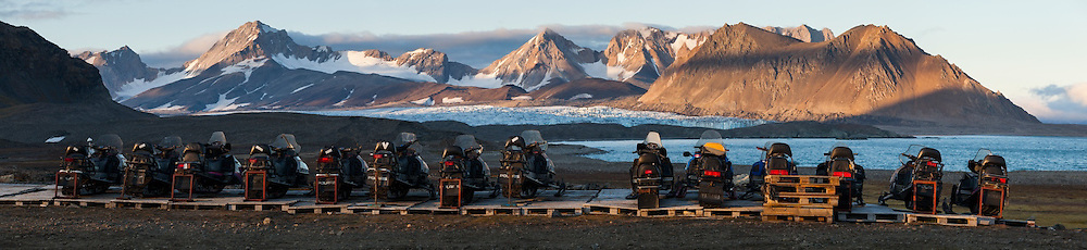 A row of snowmobiles outside the Polish Polar Station in Hornsund, Svalbard. Snowmobiles are the primary mode of long-distance transportation during the winter, when the ground is covered in snow and the fjords covered in sea ice. Hansbreen is visible in the distance.