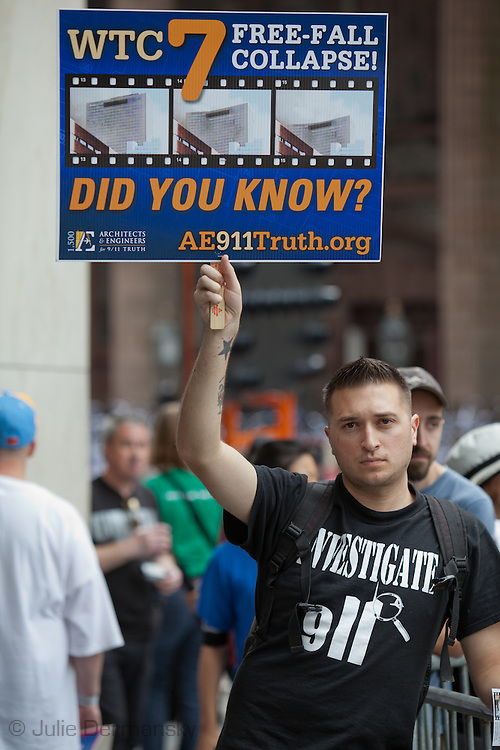 Christian Vance holds up a 'Remember building 7' sign at a rally to find out the truth about September 11th held on 10th anniversary of the 9/11 attacks on the World Trade Center towers across from St Paul's Chapel near ground zero. The 9/11 Truth Movement started in 2006 by family members who want answers about what happened on 9/11and have staged rallies at Ground Zero every year on 9/11.