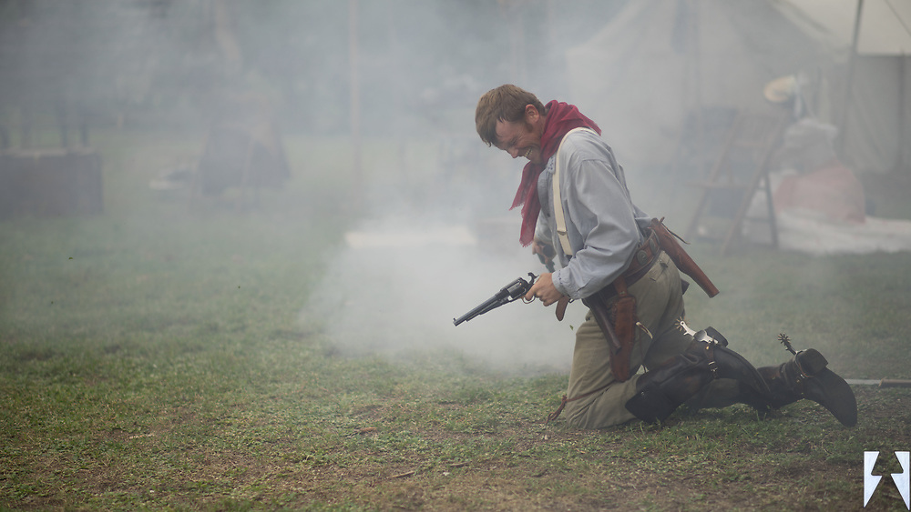 Cowboy falling in a cloud of smoke, six gun in hand, fatally shot in a gunfight over the woman in the background and gold.