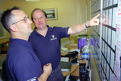 Man with disability and colleague discussing information on office wall planner,