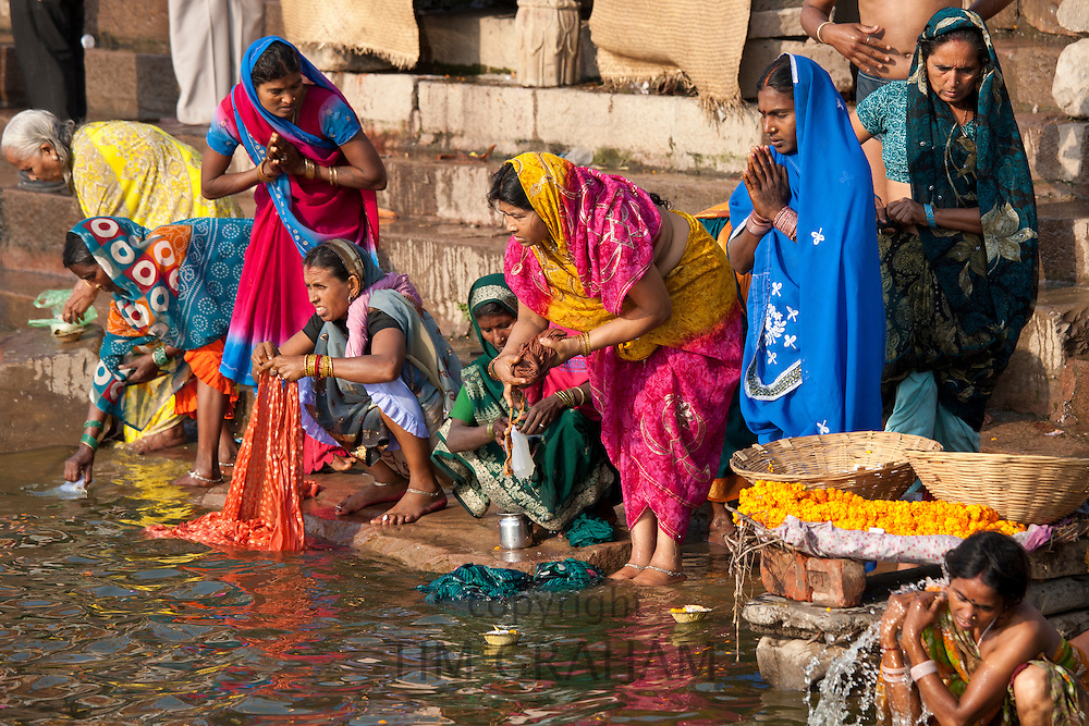 Hindu pilgrims washing clothes and bathing in The Ganges River at Dashashwamedh Ghat in Holy City of Varanasi, India RESERVED USE - NOT FOR DOWNLOAD -  FOR USE CONTACT TIM GRAHAM