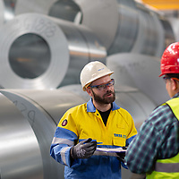TATA Steel - Distribution Centre - NEUSS - Germany - colleagues discussing steel shipment with large coil steel in background