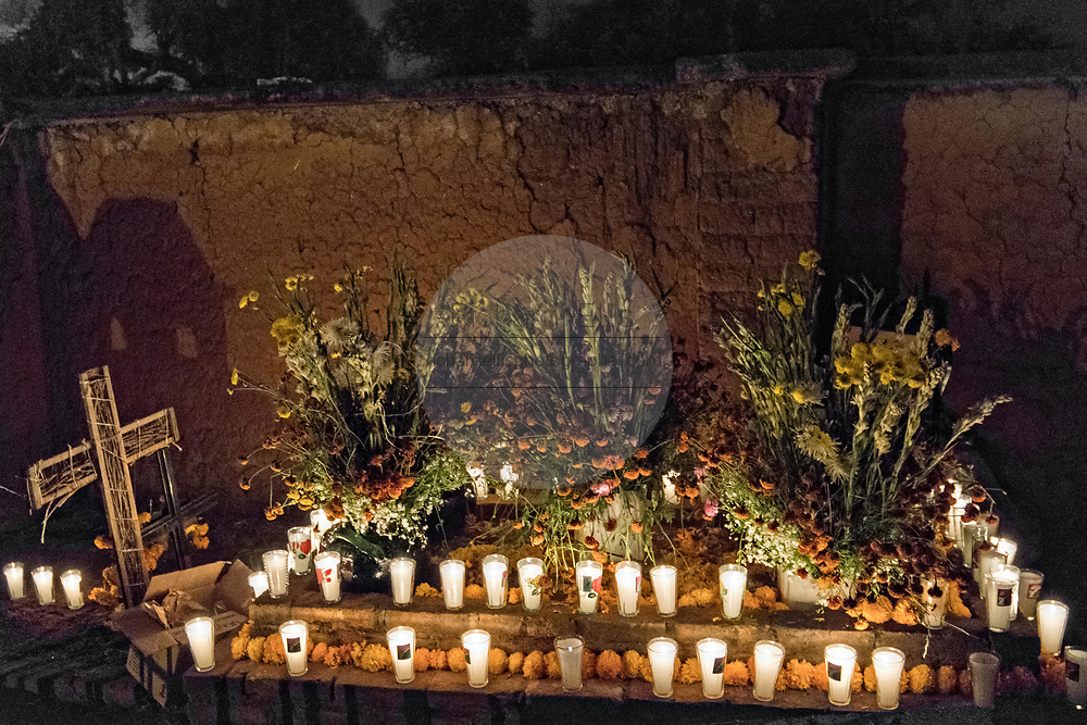 Candles light a decorated gravesite during the Day of the Dead festival October 31, 2017 in Tzintzuntzan, Michoacan, Mexico.
