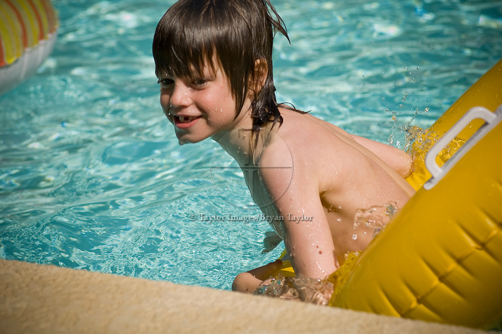 Young boy playing on a yellow float in a swimming pool.