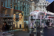 Reflection of a bus with ads and the Swarovsky jewellery shop in Londons Regent Street on 20th April 2016. A poster inside the shop shows glamorous older women wearing the watches and bangles sold by this retailer . In the background is a London Routemaster bus adorned with advertising for a fashion brand which travels its route across the capital. .