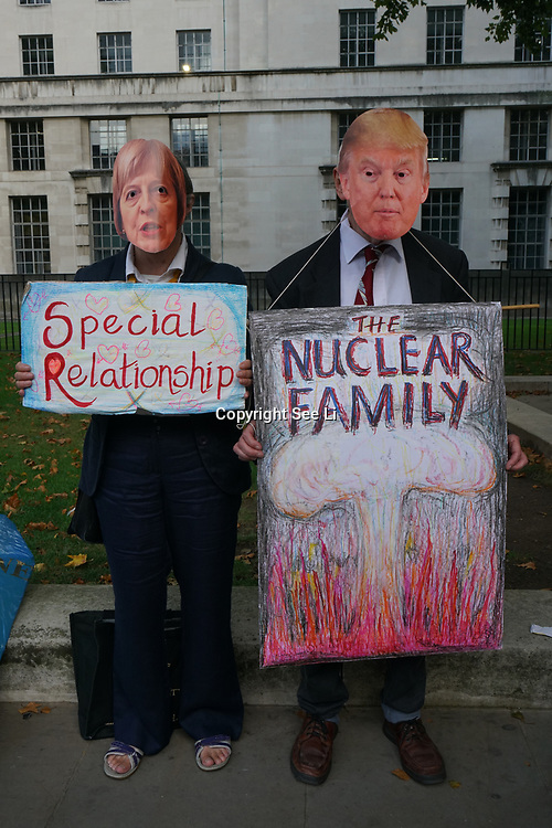 London, England, UK. 28th September 2017. A couple wearing a Theresa May and a man wearing a Trump mask protest and rally to demand Theresa May to Stop Trump and Kim Jong-Un Nuclear threat call for a peaceful solution.