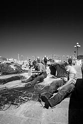 Gruppetto di pescatori gallipolini intenti a ricucire i buchi nelle loro reti da pesca.