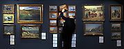 © Licensed to London News Pictures. 23/01/2012, London, UK. A man inspects a painting in the sale, Photo call at Bonhams auctioneers in Central London for 19th Century British and Euopean Paintings sale.  Photo credit : Stephen Simpson/LNP