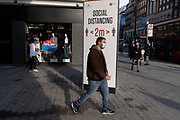 Londoners pass a social distancing sign that urges the public to keep 2 metres apart on Oxford Street during the second (Autumn) wave of the Coronavirus pandemic, on 8th October, 2020, in London, England. (Richard Baker / In Pictures via Getty Images)
