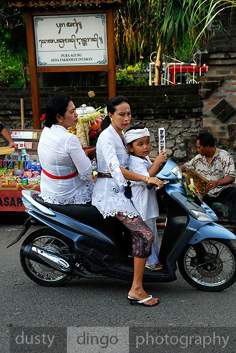 Two women, one holding temple offerings, and a small boy about to drive off on a small motorbike. Sanur, Bali, Indonesia.