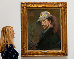 """© Licensed to London News Pictures. 25/10/2016. London, UK.  A staff member views """"Self-portrait with flowered hat, 1893"""" at the preview of Intrigue: James Ensor by Luc Tuymans.  Curated by fellow Belgian artist Luc Tuymans, this is the first exhibition of work by modernist artist James Ensor (1860-1949) to be held in the UK in twenty years and will run 29 October 2016 to 29 January 2017. Photo credit : Stephen Chung/LNP"""