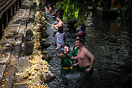 Holy Spring Water Temple (Istana Tampa Siring, close to Ubud, Bali, Indonesia.<br /> Photo shows tourists and locals bathing in the holy water and visiting the temple.