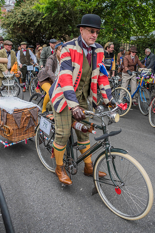 """A group brings their own towable cocktail basket - The Tweed Run - a group bicycle ride through the centre of London, in which the cyclists are expected to dress in traditional British cycling attire, particularly tweed plus four suits. Any bicycle is acceptable on the Tweed Run, but classic vintage bicycles are encouraged in an effort to recreate the spirit of a bygone era. The ride dubs itself """"A Metropolitan Cycle Ride With a Bit of Style."""" London 06 May 2017"""