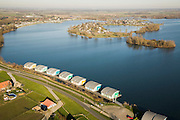 Nederland, Gelderland, Maasbommel, 11-02-2008; floating houses in the river Maas, rise and fall with the water; drijvende woningen in het water van recreatiegebied De Gouden Ham, onderdeel van de rivier de Maas; de recreatiewoningen maken onderdeel uit van een complex van buitendijks gebouwde tweede huizen, die (gaan) drijven bij hoog water; de woningen zijn bevestigd aan meerpalen om verschillen in waterhoogte op te vangen; camping met dagecreatie en stacaravans op het eiland in deze rivierbocht; ruimte voor de rivier, wateroverlast, hoog water, waterhuishouding, waterbeheer, watermanagement, wonen, water, klimaatverandering, global warming, milieu, waterwoningen, innovatie;.room for the river, flooding, high water, water resources, water management, water management, climate change, global warming, environment, living, water, housing, innovation, climate change, carbon dioxide, greenhouse gases, warming of the planet.luchtfoto (toeslag); aerial photo (additional fee required); .foto Siebe Swart / photo Siebe Swart