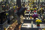 A man puts a candle on a grave of a deceased loved one at the Rakowicki cemetery in Krakow, Poland 2019.