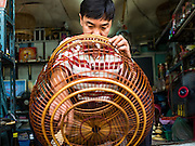 27 AUGUST 2016 - BANGKOK, THAILAND: Sarayut Nilbai, who makes and repairs birdcages, says he is the third generation of his family to live in the Pom Mahakan slum. He is varnishing a bird cage he made in his home workshop. The Pom Mahakan community is known for fireworks, fighting cocks and bird cages. Mahakan Fort was built in 1783 during the reign of Siamese King Rama I. It was one of 14 fortresses designed to protect Bangkok from foreign invaders. Only two of the forts are still standing, the others have been torn down. A community developed in the fort when people started building houses and moving into it during the reign of King Rama V (1868-1910). The land was expropriated by Bangkok city government in 1992, but the people living in the fort refused to move. In 2004 courts ruled against the residents and said the city could evict them. The city vowed to start the evictions on Sept 3, 2016, but this week Thai Prime Minister Gen. Prayuth Chan-O-Cha, sided with the residents of the fort and said they should be allowed to stay. Residents are hopeful that the city will accede to the wishes of the Prime Minister and let them stay.       PHOTO BY JACK KURTZ