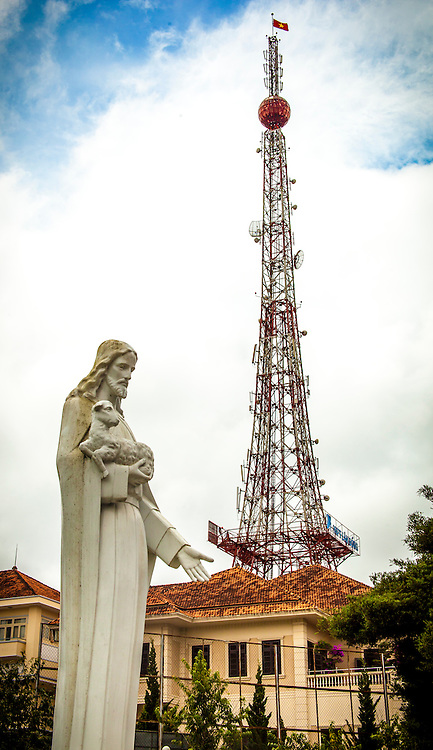 Statue of Jesus Christ carrying a lamb. Radio tower in background. Dalat, Vietnam, Asia