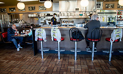 Kim Kaseta waits for her pattie melt while sitting at the counter at the Waffle House in Brookhaven Monday, April 27, 2020. The bags covering the chairs indicate where customers can't sit. Photo by Steve Schaefer/Atlanta Journal-Constitution/TNS/ABACAPRESS.COM