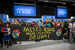 """11 December 2019, Madrid, Spain: """"Rich countries pay your debt"""" reads a sign, as hundreds of civil society and other actors hold an unauthorized protest outside the plenary hall of COP25 in Madrid, to draw attention to the failures of the climate talks and to call on rich countries to step up and pay up for real solutions, and to highlight the threat of loopholes, false solutions like carbon markets, and the need for those who caused the climate crisis to pay up for loss and damage while respecting human rights."""